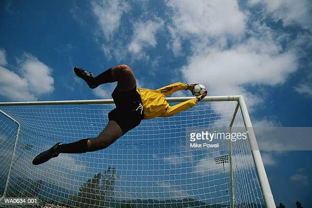 Football, goalkeeper diving to save ball, low angle view
