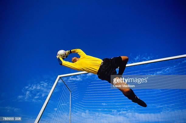 football, goalkeeper in mid jump, goal in background, low angle view - defender soccer player stock pictures, royalty-free photos & images