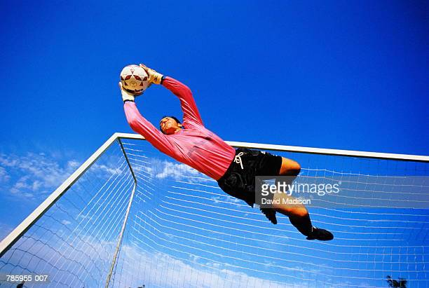 football, goalkeeper making save, low angle view - shooting at goal photos et images de collection
