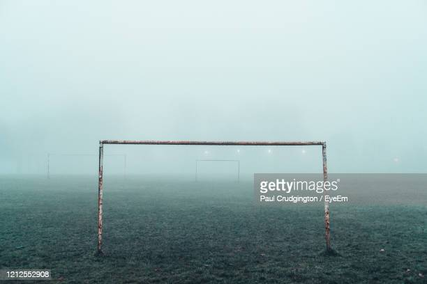 a football goalpost sits in a foggy park. - fog stock pictures, royalty-free photos & images