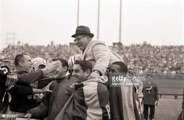 Football Green Bay Packers coach Vince Lombardi victorious getting carried off field by team after winning game vs New York Giants Milwaukee WI...
