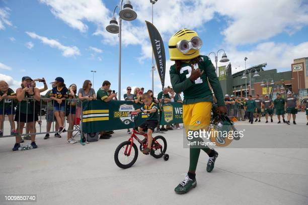 Green Bay Packers Davon House with a mascot head and a fan biking into entrance for training camp at Lambeau Field Green Bay WI CREDIT Jeff Haynes
