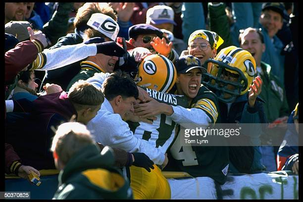 Green Bay Packers Robert Brooks victorious w fans in stands after scoring TD Brooks leaping into fans arms