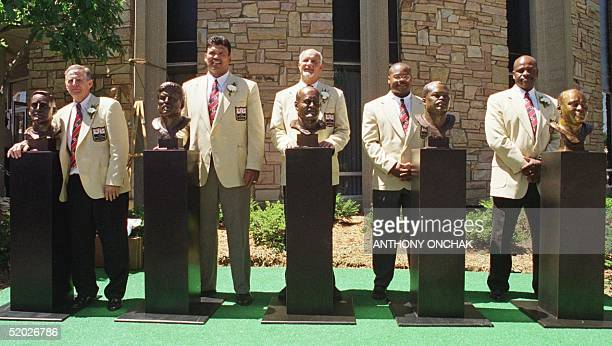 Football Hall of Fame honorees pose by their bronze busts 01 August in Canton OH after being inducted into the ProFootball Hall of Fame From L are...