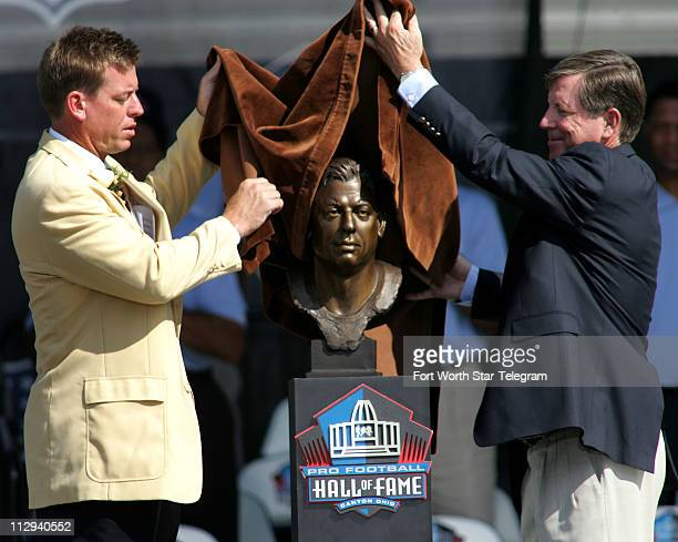 Football Hall of Fame inductee Troy Aikman left gets help from Norv Turner in unveiling his bust at the Hall's ceremony on Saturday August 5 in...
