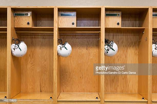 football helmets hanging in locker room - locker room stock pictures, royalty-free photos & images