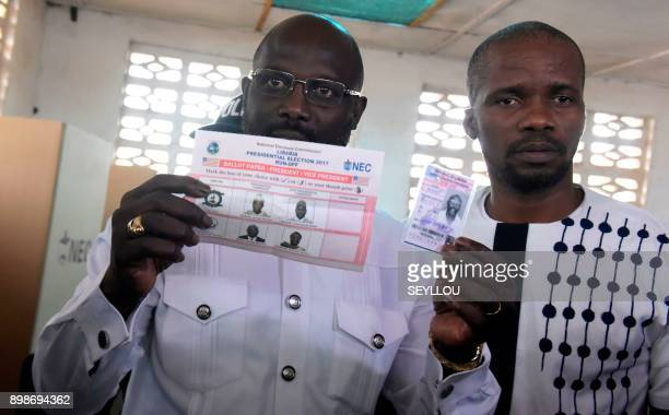Football icon and candidate for the president election for the Coalition for Democratic Change party George Weah presents his voting ballot and...