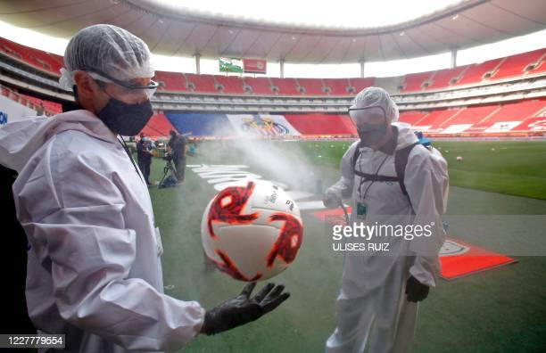 Football is disinfected before the beginning of a Mexican Apertura tournament football match between Guadalajara and Leon at the Akron stadium in...