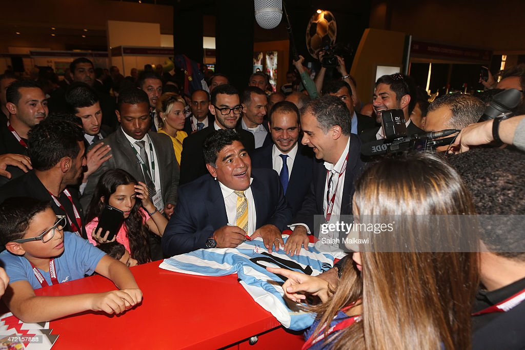 Football legend Diego Armando Maradona signs Argentine shirt as he tours the exhibition of Soccerex on the second day of Soccerex convention, the world's largest football business event in Jordan bringing together global leaders in the business of football to debate network and do business on May 4, 2015 at the King Hussein convention centre, Dead Sea, Jordan.