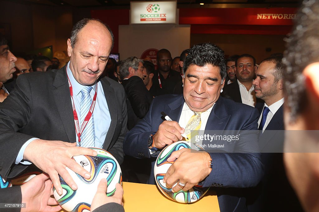 Football legend Diego Armando Maradona signs Jordanian national team shirts and footballs as he tours the exhibition of Soccerex on the second day of Soccerex convention, the world's largest football business event in Jordan bringing together global leaders in the business of football to debate network and do business on May 4, 2015 at the King Hussein convention centre, Dead Sea, Jordan.