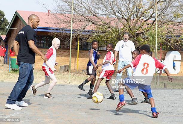 Football legends Socrates of Brazil and Quinton Fortune of Manchester United and South Africa play football with some of the kids from the 1GOAL...
