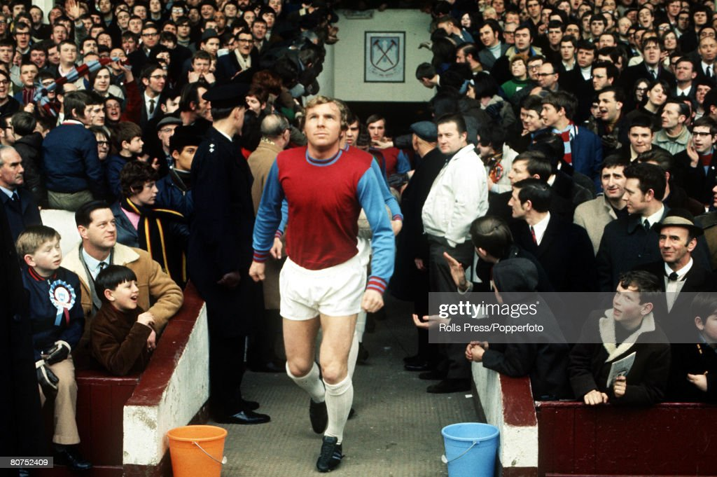 Football London, 1970. West Ham captain Bobby Moore leads out his team before a game at Upton Park as the crowd watches. : News Photo