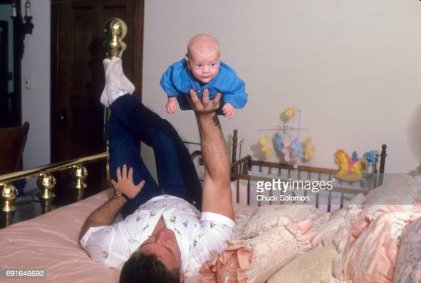 Los Angeles Raiders Howie Long laying in bed holding up his baby son Christopher during photo shoot at home Boston MA CREDIT Chuck Solomon