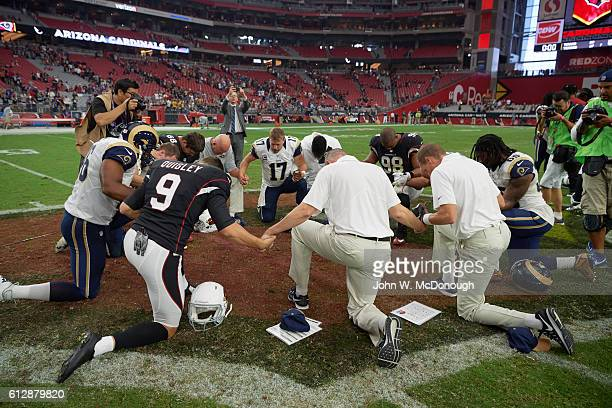 Los Angeles Rams QB Case Keenum and Arizona Cardinals Corey Peters during postgame prayer circle after game at University of Phoenix Stadium Glendale...