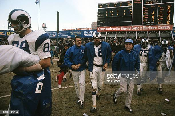 Los Angeles Rams QB Roman Gabriel victorious on field after winning game vs New York Giants at Yankee Stadium. View of scoreboard reading Rams 31,...