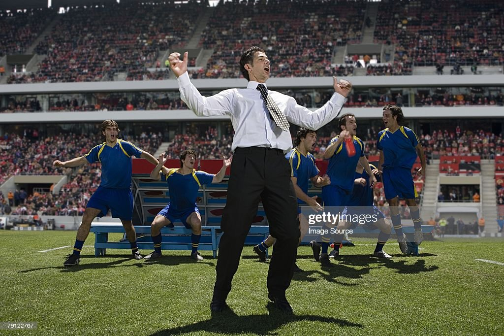 Football manager and footballers celebrating : Stock Photo