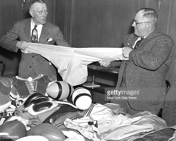 Football meeting at Hotel Biltmore Coach Jock Sutherland of Bklyn and Steve Owen coach of N Y Giants pull on new Tuway stretch pants that will be...