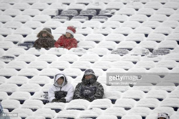 New England Patriots fans sitting on snow covered seats in stands before game vs Arizona Cardinals Foxboro MA CREDIT Damian Strohmeyer