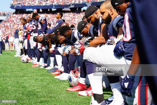 New England Patriots players kneeling on sidelines with arms linked during National Anthem before game vs Houston Texans at Gillette Stadium...
