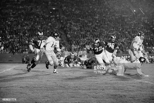 New York Giants Frank Gifford in action rushing under pressure Los Angeles Rams Deacon Jones during preseason game at Los Angeles Memorial Coliseum...