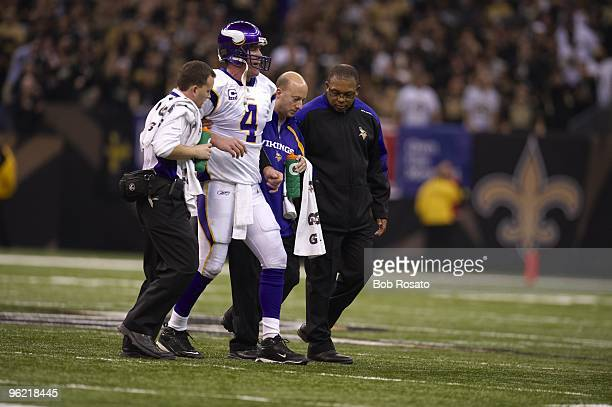 NFC Playoffs Minnesota Vikings QB Brett Favre walking off field during injury with trainers during game vs New Orleans Saints New Orleans LA...