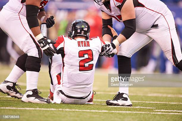 NFC Playoffs Rear view of Atlanta Falcons QB Matt Ryan being helped up from filed by teammates during game vs New York Giants at MetLife Stadium East...