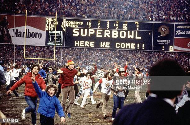 Football NFC playoffs San Francisco 49ers fans victorious on field after winning game vs Dallas Cowboys View of scoreboard with SUPER BOWL HERE WE...