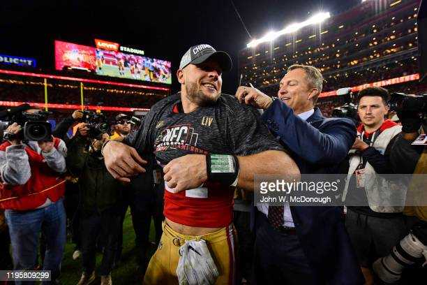 NFC Playoffs San Francisco 49ers Nick Bosa with general manager John Lynch helping him put on NFL Championship tee shirt on field after winning game...