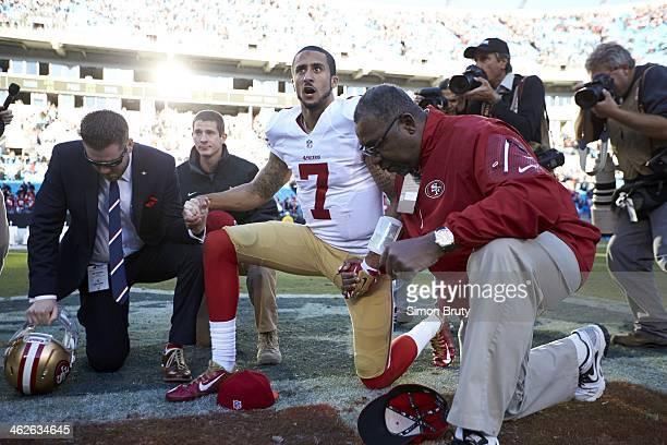NFC Playoffs San Francisco 49ers QB Colin Kaepernick kneeling in prayer on field after game vs Carolina Panthers at Bank of America Stadium Charlotte...