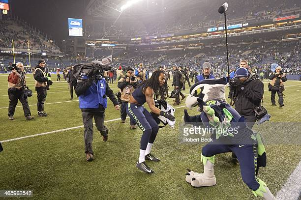 NFC Playoffs Seattle Seahawks Richard Sherman victorious with mascot Blitz after winning game vs Carolina Panthers at CenturyLink Field Seattle WA...