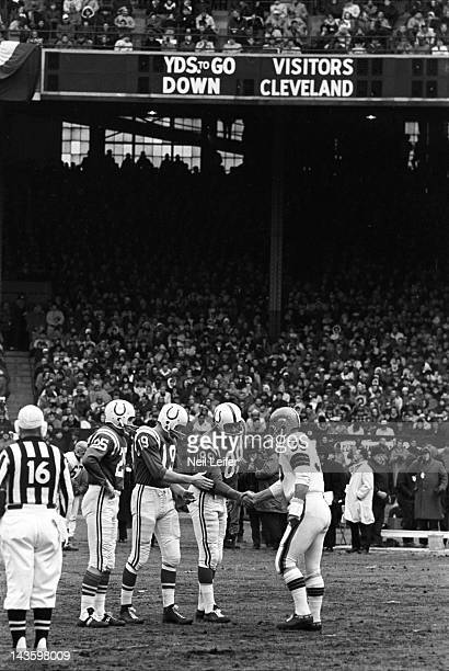 NFL Championship Cleveland Browns Ted Davis shaking hands with Baltimore Colts Gino Marchetti QB Johnny Unitas and Alex Hawkins before game at...
