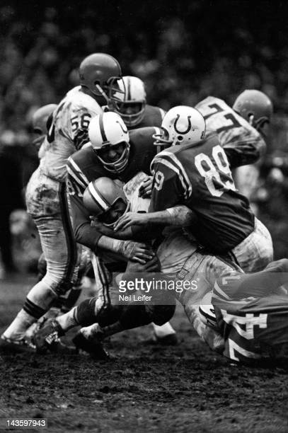 NFL Championship Cleveland Browns Jim Brown in action vs Baltimore Colts Ordell Braase and Gino Marchetti at Cleveland Municipal Stadium Cleveland OH...