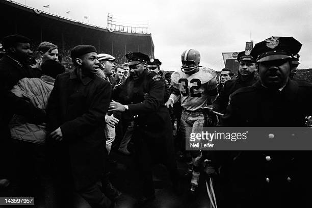 NFL Championship Cleveland Browns Jim Brown victorious leaving field with police escort after winning game vs Baltimore Colts at Cleveland Municipal...
