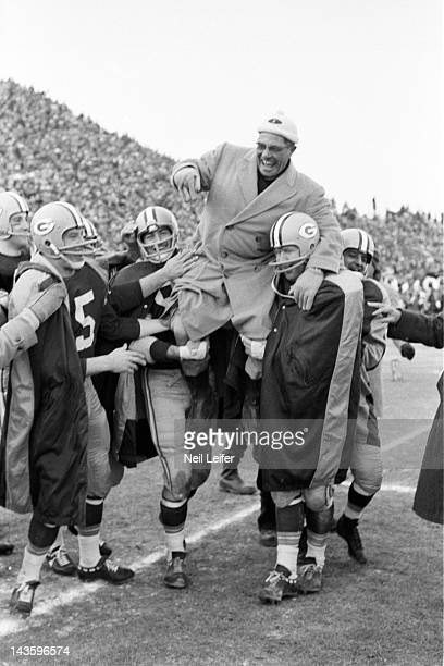 NFL Championship Green Bay Packers head coach Vince Lombardi victorious getting carried off field by players after winning game vs New York Giants at...