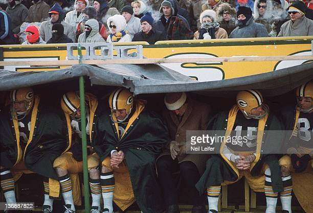 Football NFL Championship Green Bay Packers QB Bart Starr and teammates huddled under tarp on sidelines during Ice Bowl game vs Dallas Cowboys at...