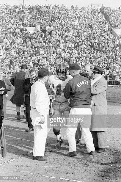 NFL Championship New York Giants Kyle Rote walking off field after sustaining injury during game vs Baltimore Colts at Memorial Stadium Baltimore MD...