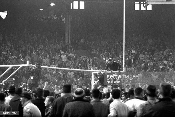 NFL Championship View of fans victorious climbing goal posts on field after Baltimore Colts vs New York Giants game at Memorial Stadium Baltimore MD...