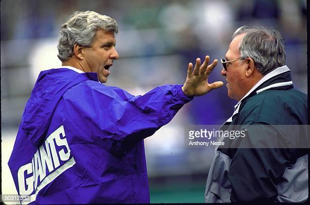 Giants coach Bill Parcells on field talking w. Phila. Eagles coach Buddy Ryan before game.