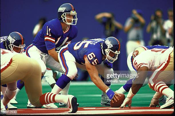 Giants QB Phil Simms at line at scrimmage during game vs SF 49ers. Simms under teammate Bart Oates waiting for snap.