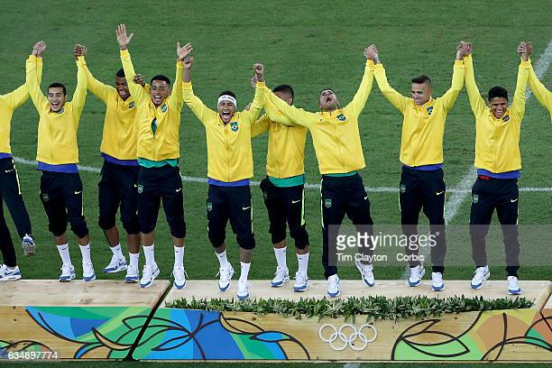 Day 15 Neymar of Brazil wearing a head band and his teammates celebrate their gold medal win on the podium during the Brazil Vs Germany Men's...