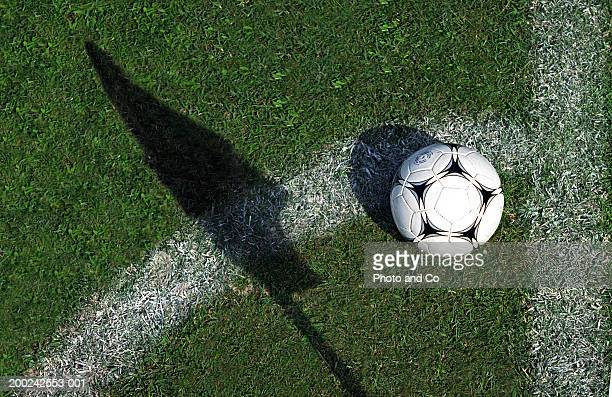 football on grass by pitch marking and shadow of flag - fussball stock-fotos und bilder