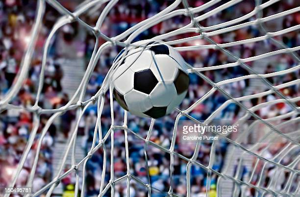 football, or soccer ball in the back of a net - marquer un but photos et images de collection