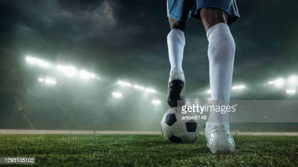 football or soccer player on full stadium and flashlights background - kicking stock pictures, royalty-free photos & images