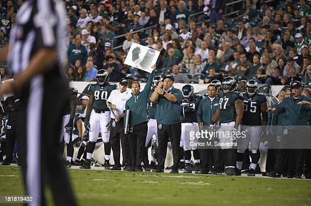 Philadelphia Eagles coach holding Phillie Phanatic sign to signal play from sidelines during game vs Kansas City Chiefs at Lincoln Financial Field...