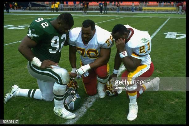 Philadelphia Eagles Reggie White on field with Washington Redskins Tim Johnson and Earnest Byner Praying