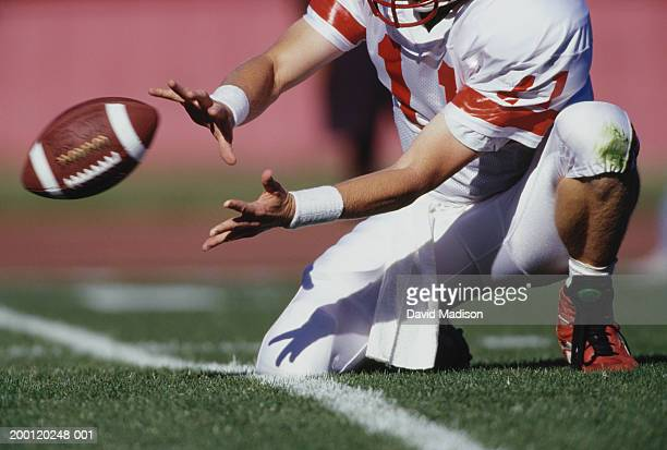 football placekicker holder prepares to catch ball, low section - catching stock pictures, royalty-free photos & images