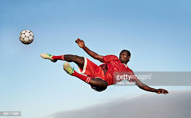 football player about to kick ball in the air - fußballspieler stock-fotos und bilder