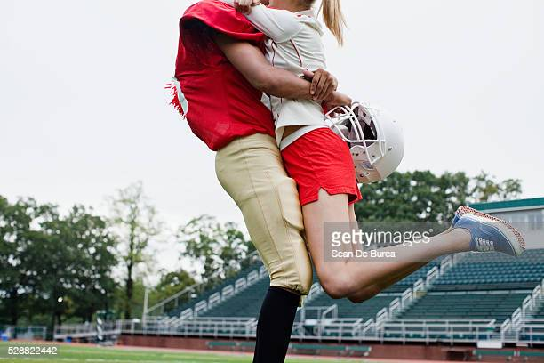 Football player and cheerleader hugging