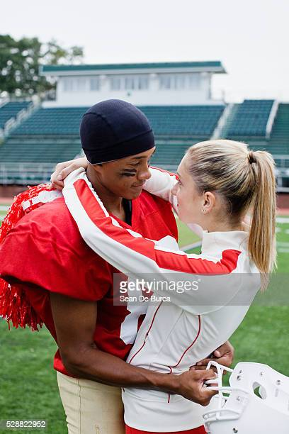 football player and cheerleader hugging - candid cheerleaders stock photos and pictures