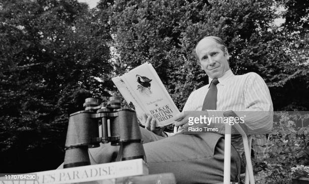 Football player Bobby Charlton reading the 'Book of British Birds' outdoors, with a pair of binoculars, 1973.